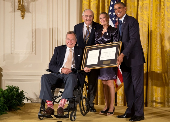 President Barack Obama and former President George H. W. Bush present the 5,000th Daily Point of Light Award to Outreach Inc. co-founders Floyd Hammer and Kathy Hamilton, winners of the 5,000th Daily Point of Light Award, in the East Room of the White House, July 15, 2013. (Official White House Photo by Pete Souza)
